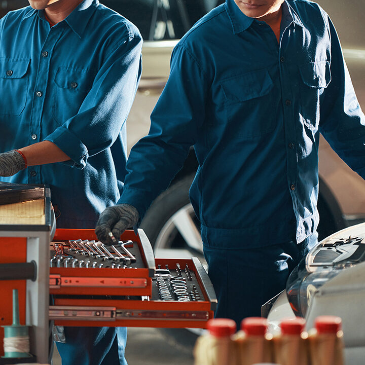 Cropped image of mechanic in uniform taking wrench out of draw when repairing car in garage
